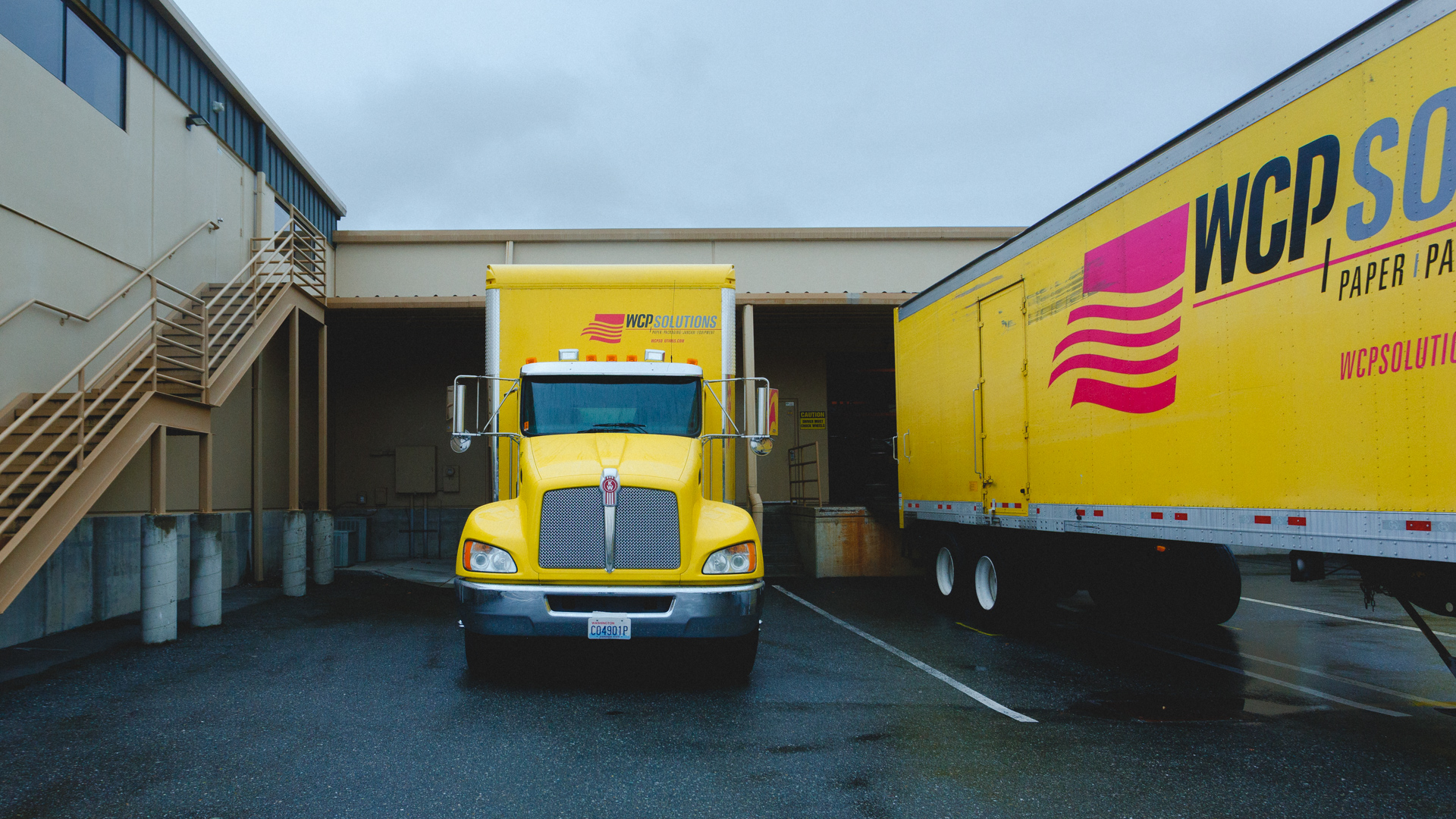 WCP Solutions' big yellow truck parked in front of loading dock at a warehouse